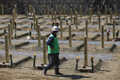 A file picture dated 5 April 2011 shows Mayor of the Urashuku First Ward and an emergency volunteer firefighter Fumio Hiratsuka, 76, looking for his missing relatives at a makeshift mass grave for tsunami victims in the coastal town of Onagawa, Miyagi prefecture, northeastern Japan. (Photo: AAP).