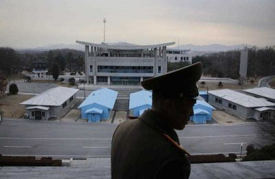 Korean People's Army Lt. Col. Nam Dong Ho is silhouetted against the truce village of Panmunjom at the Demilitarized Zone (DMZ), which separates the two Koreas, in Panmunjom, North Korea. (Photo: AAP).