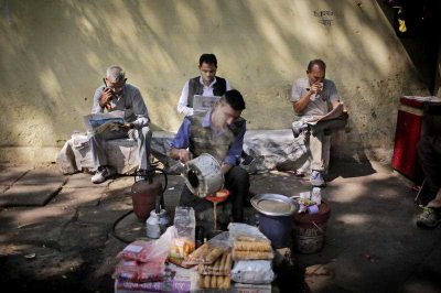 An Indian roadside tea vendor prepares tea for people reading newspapers in New Delhi, India, Tuesday, 1 March  2016. (Photo: AAP).