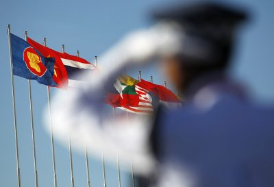 A police officer stands near national flags of ASEAN counties during the 25th ASEAN Summit in Myanmar. (Photo: Reuters).