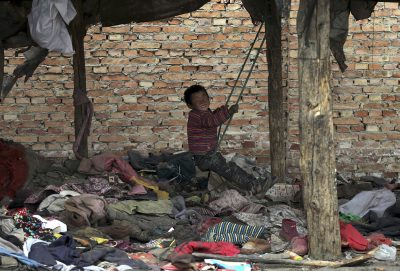 A boy, whose parents collect garbage for a living, plays on a makeshift swing at his dwelling, in Yuncheng, Shanxi province, 10 March 2015. (Photo: Reuters).
