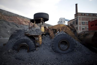 An abandoned excavator is partially covered by coal waste at a mine of the state-owned Longmay Group on the outskirts of Jixi, in Heilongjiang province, China. (Photo: Reuters/Jason Lee).