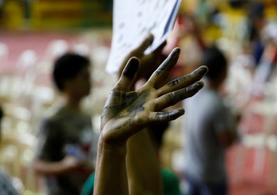 A drug user raises his ink-smeared hand after he surrendered to local government officials to take part in a government campaign against drugs in Tanauan Batangas, Philippines, 18 July 2016. (Photo: Reuters/Erik De Castro).