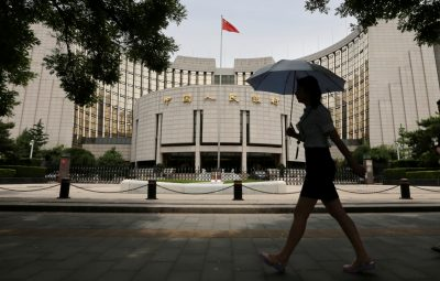A woman walks past the headquarters of the People's Bank of China (PBoC), the central bank, in Beijing, 24 June 2016 (Photo: Reuters/Jason Lee).