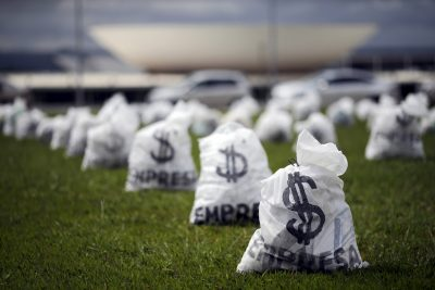 Replica of bags full of money can be seen in front of the National Congress during a protest symbolising the donations of private companies for election campaigns, Brazil, 24 March, 2015. (Photo: Reuters/Ueslei Marcelino).