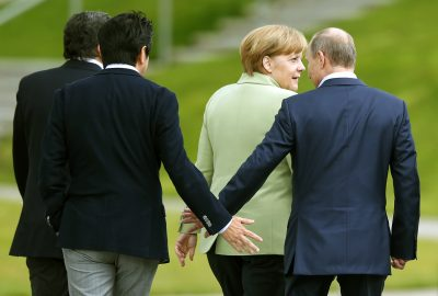Japan's Prime Minister Shinzo Abe (2nd L) touches hands with Russia's President Vladimir Putin as they walk with Germany's Chancellor Angela Merkel, after a G8 summit group photograph was taken at the Lough Erne golf resort in Enniskillen, Northern Ireland, United Kingdom, 18 June 2013. (Photo: Reuters/Andrew Winning).