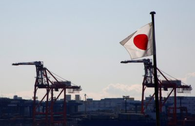Japan's national flag is seen in front of containers and cranes at an industrial port in Tokyo, Japan, 25 January 2017 (Photo: Reuters/Kim Kyung-Hoon).