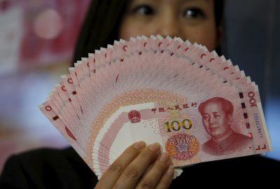 100 renminbi notes held up at the Bank of China Tower in Hong Kong, 12 November 2015. (Photo: Reuters/Bobby Yip).