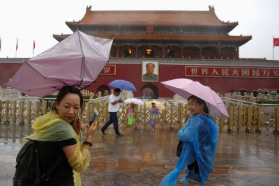 Tourists hold umbrellas as they stand in front of the Tiananmen Gate and a giant portrait of Chinese late Chairman Mao Zedong on a day of heavy rain in Beijing, China, 20 July 2016 (Photo: Reuters/Thomas Peter).