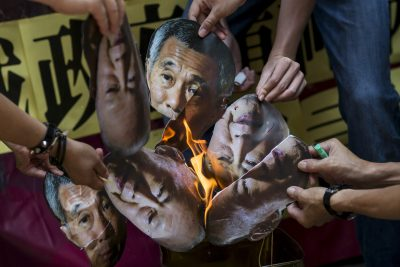 Protesters burn pictures of Singapore's first Prime Minister Lee Kuan Yew and his son and current Prime Minister Lee Hsien Loong outside the Singapore Consulate in Hong Kong, China, 5 July 2015 (Photo: Reuters/Tyrone Siu).