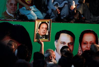 A supporter of former Pakistani prime minister Nawaz Sharif holds his picture as he waits for his convoy to pass through in Rawalpindi, Pakistan, 10 August 2017. (Photo: Reuters/Faisal Mahmoud).