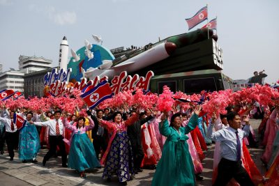 People react as they march past foreign journalists and the stand with North Korean leader Kim Jong Un during a military parade marking the 105th birth anniversary of the country's founding father Kim Il Sung in Pyongyang 15 April 2017