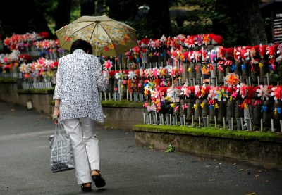 An elderly woman walks past jizo statues, dedicated to the growth of children and grandchildren, which also act as a memorial for miscarried children, decorated with colourful pinwheels and flowers at a Buddhist temple in Tokyo, Japan, 30 June 2017 (Photo: Reuters/Toru Hanai).