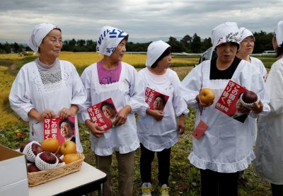 Women hold leaflets of the Liberal Democratic Party's election campaign featuring Japanese Prime Minister Shinzo Abe's photo while they wait for an election campaign rally in Fukushima, Japan, 10 October, 2017 (Photo: Reuters/Toru Hanai).