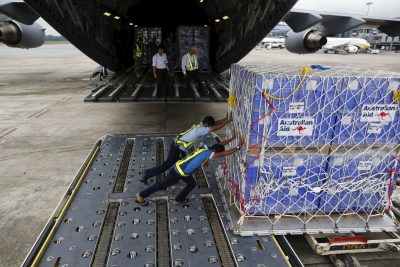 Workers unload aid from an Royal Australian Air Force transport plane carrying donated aid for Myanmar's flood victims at Yangon international airport, 10 August 2015 (Photo: Reuters/Soe Zeya Tun).
