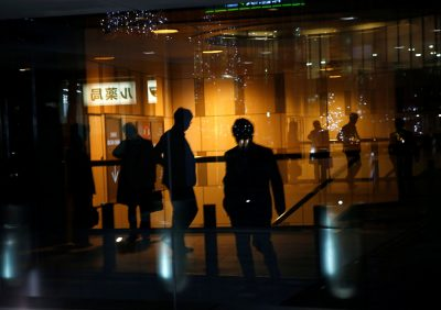 Pedestrians are reflected on a window of a commercial building at closing hour at a financial district in Tokyo, Japan, 22 November 2017 (Photo: Reuters/Kim Kyung-hoon).