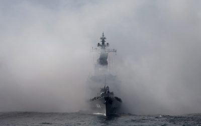 Japan's Maritime Self-Defense Force destroyer Kurama, which is carrying Japan's Prime Minister Shinzo Abe, sails in smoke during its fleet review at Sagami Bay south of Tokyo, 18 October 2015 (Photo: Reuters/Toru Hanai).