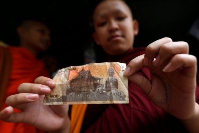 A Buddhist monk holds a riel banknote with the image of Buddha at a store in Phnom Penh, Cambodia, 22 August 2017 (Photo: Reuters/Samrang Pring).