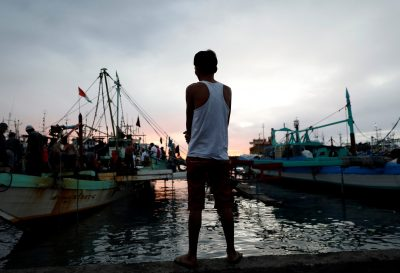 A man, whose wife was arrested during an anti-drug operation and was found dead a day later, stands near fishing boats in Navotas, Metro Manila, Philippines, 5 December 2017 (Photo: Reuters/Dondi Tawatao).