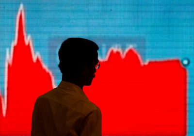 A man walks past a screen displaying news of markets update inside the Bombay Stock Exchange building in Mumbai, India, 6 February 2018 (Photo: Reuters/Danish Siddiqui).