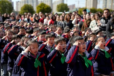 Pupils salute during a flag raising ceremony on their first day of the new semester at a primary school in Shanghai, China, 23 February 2018 (Photo: Reuters/Aly Song).