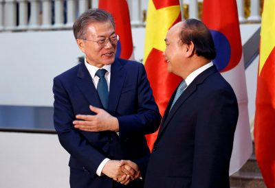 South Korea's President Moon Jae-in chats with Vietnam's Prime Minister Nguyen Xuan Phuc while posing for
