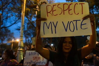 A protester holds a placard as she gathers with others during a protest against junta near the army headquarters in Bangkok, Thailand, 24 March 2018 (Photo: Reuters/Panumas Sanguanwong).