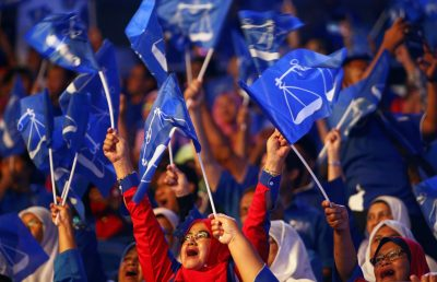 Supporters of Malaysia's ruling party National Front waves the party flags during the launch of its manifesto for the upcoming general elections in Kuala Lumpur, Malaysia, 7 April 2018 (Photo: Reuters/Lai Seng Sin).
