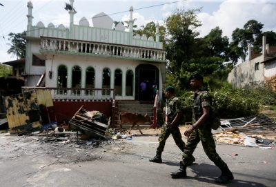 Sri Lanka's Special Task Force soldiers walk past a damaged mosque after a clash between two communities in Digana, central district of Kandy, Sri Lanka, 8 March 2018 (Photo: Reuters/Dinuka Liyanawatte).