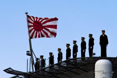 Sailors stand on the deck of the Izumo warship as it departs from the harbour of the Japan United Marine shipyard in Yokohama on 25 March 2015. (Photo: Reuters/Thomas Peter.)