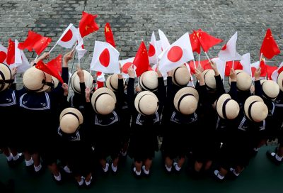 Kindergarten pupils wave national flags as Chinese Premier Li Keqiang reviews the guard of honour with Japan's Prime Minister Shinzo Abe during a welcoming ceremony before their bilateral talks at Akasaka Palace state guest house in Tokyo, Japan, 9 May 2018 (Photo: Reuters/Toru Hanai).