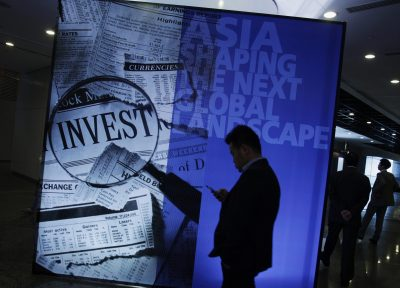 A participant stands in front of a backdrop during the Asian Financial Forum in Hong Kong on 14 January 2013. China can increase 10 times the current level of investment quotas for Renminbi Qualified Foreign Institutional Investment (RQFII) and QFII, Guo Shuqing, chairman of the China Securities Regulatory Commission (CSRC), said on Monday at the Asia Financial Forum in Hong Kong (Photo: Reuters/Bobby Yip).
