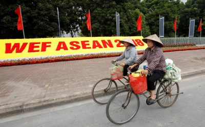 Vietnamese women ride bicycles past the National Convention Center, the venue for World Economic Forum on ASEAN in Hanoi, Vietnam, 11 September 2018 (Photo: Reuters/Kham).