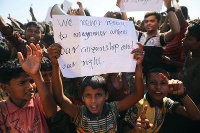 A boy holds a placard as hundreds of Rohingya refugees protest against their repatriation at the Unchiprang camp in Teknaf, Bangladesh 15 November 2018 (Photo: Reuters/Mohammad Ponir Hossain).