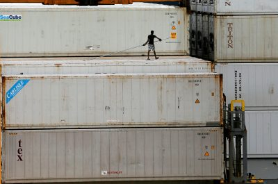 A dock worker is seen on top of shipping containers in a ship at the main port in Colombo,SriLanka, 21June 2018 (Photo: Reuters/Dinuka Liyanawatte).