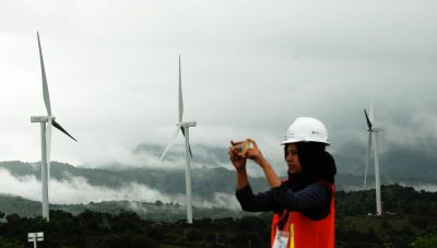 A woman takes pictures of wind power plant propeller blades in Sidenreng Rappang, Sulawesi Island of Indonesia, 15 January 2018 (Photo: Antara Foto/Yusran Uccang via Reuters).
