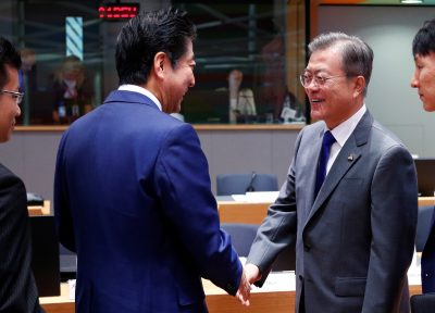 Japan's Prime Minister Shinzo Abe and South Korea's President Moon Jae-in shake hands as they attend the ASEM leaders summit in Brussels, Belgium, 19 October 2018 (Reuters/Francois Lenoir).