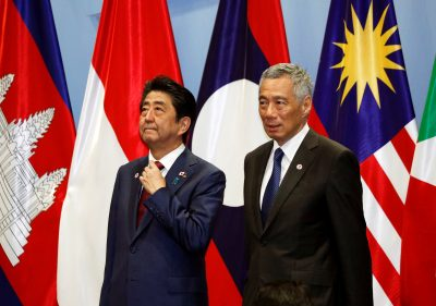 Japan's Prime Minister Shinzo Abe takes his position next to Singapore's Prime Minister Lee Hsien Loong for a group photo with ASEAN leaders at the ASEAN–Japan Summit in Singapore, 14 November 2018 (Photo: Reuters/Edgar Su).