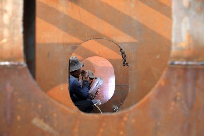 Workers weld iron sheets as they build a new ferry at a dockyard in Dhaka, Bangladesh, 7 February 2019 (Photo: Reuters/Mohammad Ponir Hossain).