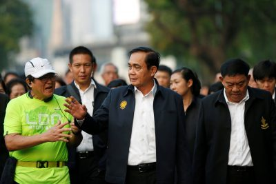 Thailand's Prime Minister Prayut Chan-o-cha talks with a man as he visits Lumphini Park ahead of the general election, in Bangkok, Thailand, 20 March 2019 (Photo: Reuters/Soe Zeya Tun).