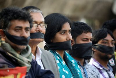 Activists of leftist alliance cover their mouth with black cloths as they join in a rally to demand a new election under caretaker government, in Dhaka, Bangladesh, 3 January 2019 (Photo: Reuters/Mohammad Ponir Hossain).