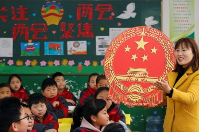 A teacher gives a lesson on the Chinese National People's Congress (NPC) and People's Political Consultative Conference (CPPCC) with a cutout of a Chinese national emblem at a primary school in Weinan, Shaanxi province, China, 4 March 2019. (Photo: Reuters/Stringer)
