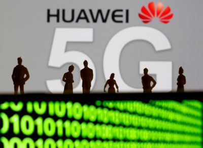 Small toy figures are seen in front of a displayed Huawei and 5G network logo 30 March 2019 (Photo: Reuters/Dado Ruvic).