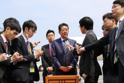 Japanese Prime Minister Shinzo Abe speaks to reporters before he leaves the Tokyo International Airport to Paris with the new government plane Boeing 777 for a eight-day visit to European and North American countries on 22 April 2019 (Photo: Reuters/Yoshio Tsunoda).