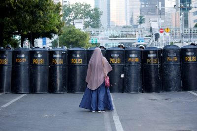 A woman stands in front of a police's barricade after a riot outside Indonesia's Election Supervisory Agency (Bawaslu) headquarters following the announcement of election results in Jakarta, Indonesia, 24 May 2019 (Photo: Reuters/Willy Kurniawan).