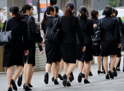 Female office workers wearing high heels, clothes and bags of the same colour make their way at a business district in Tokyo, Japan, 4 June 2019 (Photo: Reuters/Kim Kyung-Hoon).