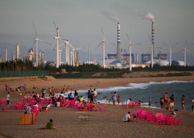 Windmills and a power plant can be seen in the distance as beachgoers watch the sunset in the city of Dongfang, Hainan, China (Photo: Reuters/John Ruwitch).