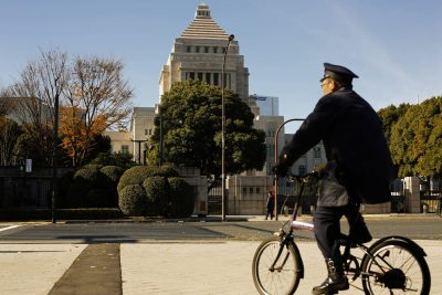 A police officer cycles past the Diet building, the seat of Japan's parliament, in Tokyo (Photo: Reuters/Thomas Peter).