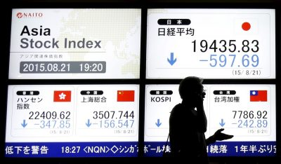 A man walks past an electronic board displaying various Asian countries' stock price index outside a brokerage in Tokyo August 21, 2015 (Photo: Reuters/Issei Kato).