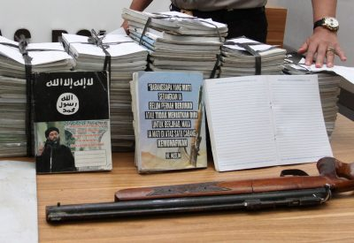 Indonesian police show scores of notebooks inscribed with Islamic State propaganda seized during a raid on the home of suspected militant in Jakarta, Indonesia, 30 June 2017 (Photo: Reuters/Antara Foto/Reno Esnir).
